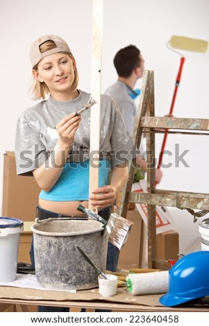 Happy casual, caucasian couple busy renovating painting new home. Baseball cap, bucket, ladder. - stock photo