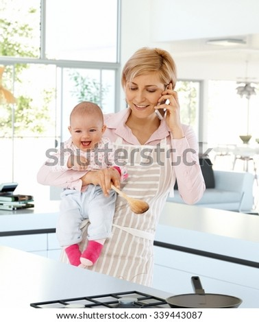 Happy, casual, caucasian housewife in kitchen with baby in hand, talking on phone. Standing, busy, cooking, wearing apron, holding wooden spoon.