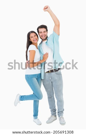 Happy casual couple cheering at camera on white background - stock photo