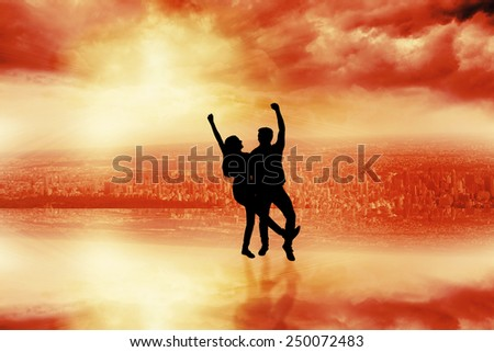 Happy casual couple cheering together against room with large window looking on city