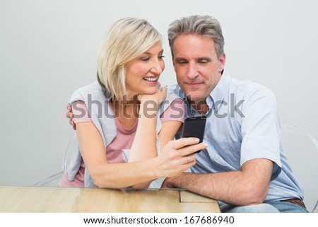 Happy casual couple looking at mobile phone in the house