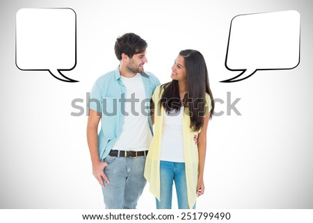 Happy casual couple smiling at each other against white background with vignette - stock photo