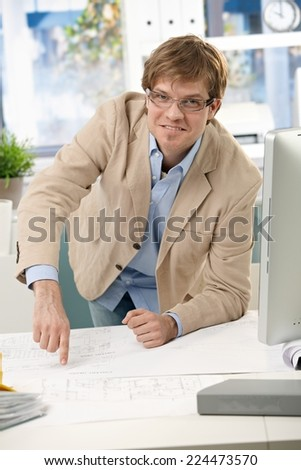 Happy casual engineer pointing at business plan on office table. Leaning on elbow, smiling, looking at camera, wearing glasses, bright. - stock photo