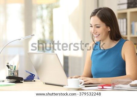 Happy casual entrepreneur working on line typing with a laptop at office with a window in the background - stock photo