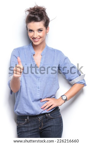 Happy casual fashion woman showing the thumbs up gesture while posing for the camera. - stock photo