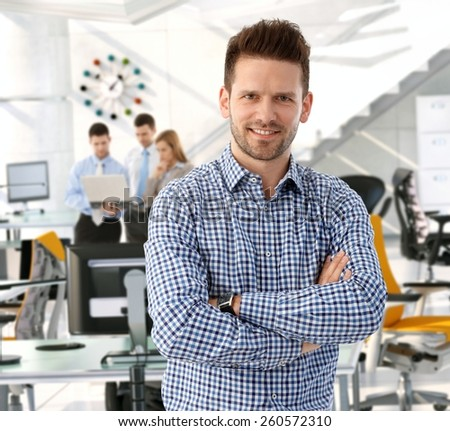 Happy casual handsome caucasian business team leader at startup office. Looking at camera, smiling, arms crossed. Confident, successful. - stock photo