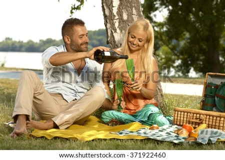 Happy casual handsome husband and blonde attractive wife drinking champagne at outdoor picnic. Smiling, sitting with basket, glasses and bottle, barefoot. - stock photo