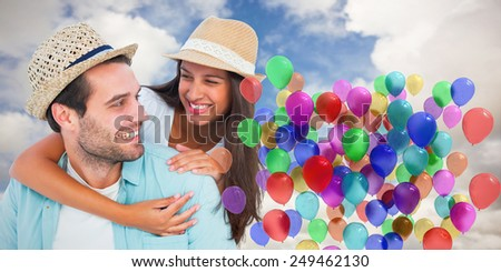 Happy casual man giving pretty girlfriend piggy back against blue sky with white clouds - stock photo