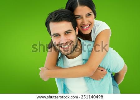 Happy casual man giving pretty girlfriend piggy back against green vignette - stock photo