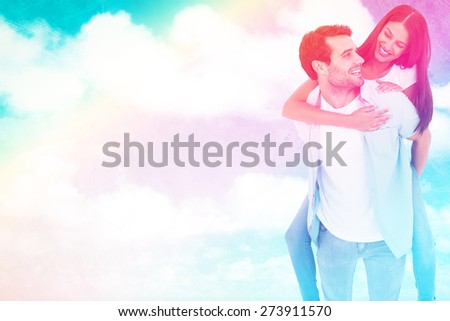 Happy casual man giving pretty girlfriend piggy back against painted sky - stock photo
