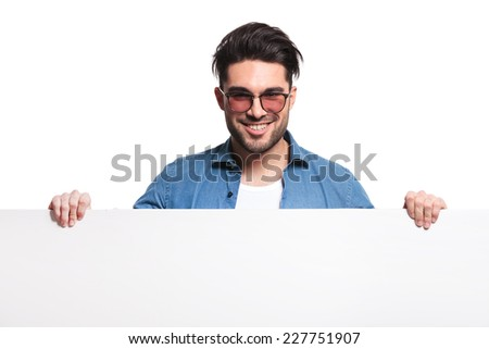 Happy casual man holding a white board while smiling for the camera.