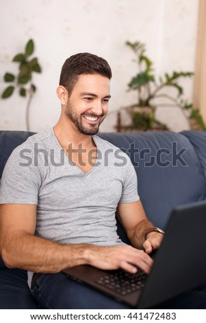 Happy casual man online communication on laptop, chat with teeth smile