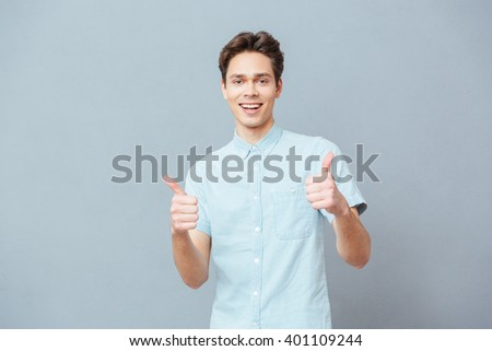 Happy casual man showing thumbs up over gray background