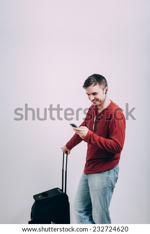 Happy casual man traveling with luggage and using mobile phone.