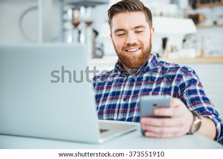 Happy casual man using smartphone and laptop computer in cafe - stock photo