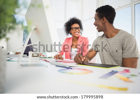 Happy casual photo editors using graphics tablet in the office - stock photo