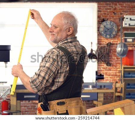 Happy casual senior handyman measuring with folding ruler at workshop. Smiling with back to camera. - stock photo