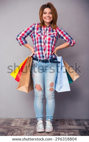 Happy casual woman holding shopping bags in studio. Looking at camera - stock photo
