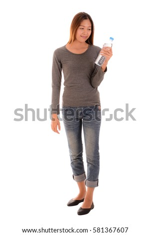 Happy casual woman is standing and holding a  bottle of  water on white background.