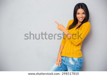 Happy casual woman showing finger away over gray background - stock photo