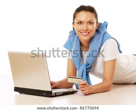 Happy casual woman with credit card and laptop lying on floor isolated