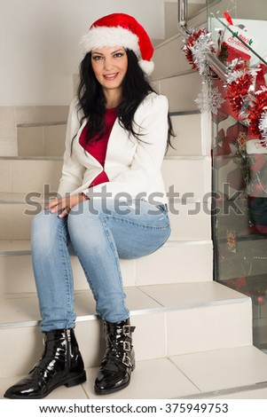 Happy casual woman with Santa hat posing  on stairs home