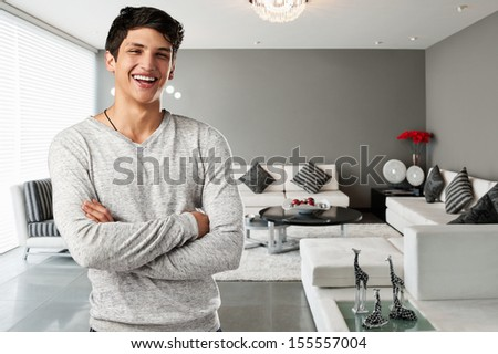 Happy casual young man at modern apartment - stock photo