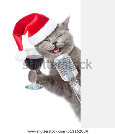 Happy cat with wineglass and retro microphone in red christmas hat peeking from behind empty board. isolated on white background