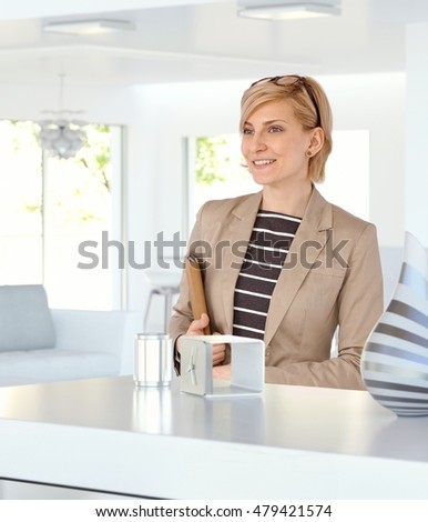 Happy caucasian blonde woman at home with folder in hand. Smiling, wearing glasses and jacket. Business papers.