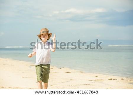 Happy caucasian boy enjoing summer on tropical beach - stock photo