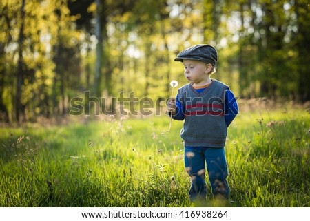 Happy caucasian boy playing outdoor at warm springtime day - stock photo