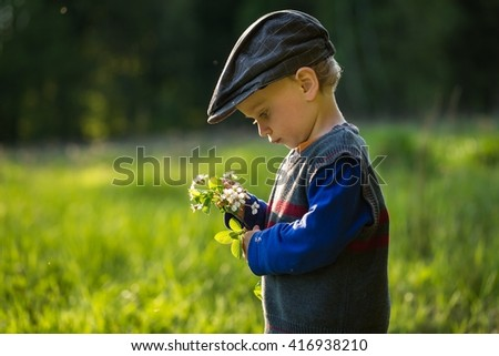 Happy caucasian boy playing outdoor at warm springtime day, boy holding blooming cherry branch - stock photo
