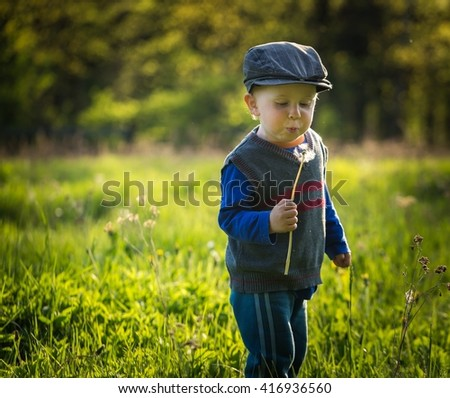 Happy caucasian boy playing outdoor at warm springtime day, boy playing with dandelion - stock photo