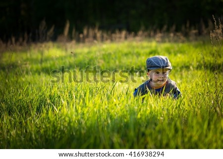 Happy caucasian boy playing outdoor in high grass at warm springtime day - stock photo
