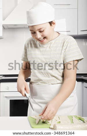 Happy caucasian boy slicing dough while cooking at the kitchen - stock photo