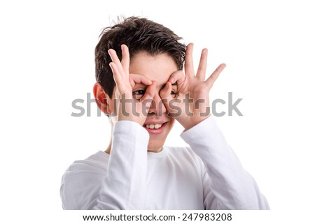 Happy Caucasian boy with acne skin in a white long sleeve t-shirt is making fan placing his hands on face as a mask - stock photo