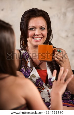 Happy Caucasian brunette drinking coffee and talking with friend - stock photo