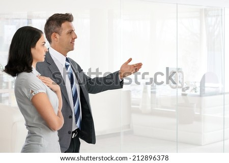 Happy caucasian businessman in suit presenting new possibility, achievement with hand to businesswoman at business office. Standing, copyspace. - stock photo