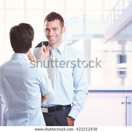 Happy caucasian businessman with colleague at business office, standing, smiling, looking at camera, hand in pocket, suit jacket on back. Copyspace. - stock photo
