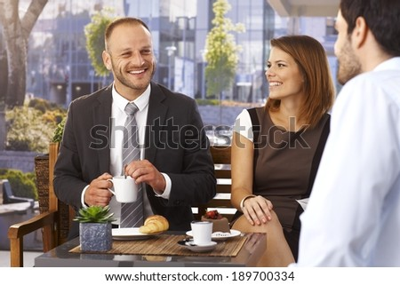 Happy caucasian businessmen and businesswoman relaxing, having a break at the cafe in the morning, outdoor. - stock photo