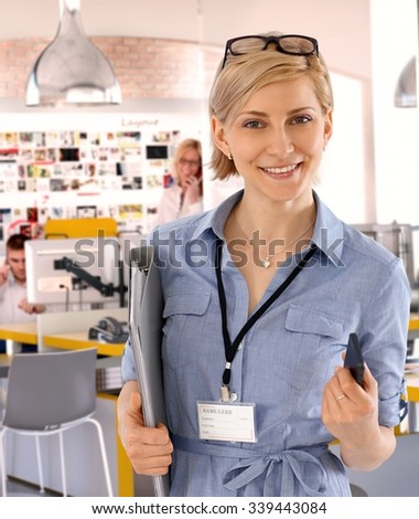 Happy caucasian casual blonde assistant worker at business office, standing, holding a folder, wearing glasses and a name card, tag, Smiling, looking at camera.