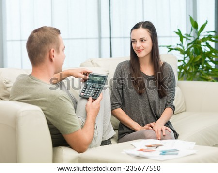 happy caucasian couple calculating budget at home
