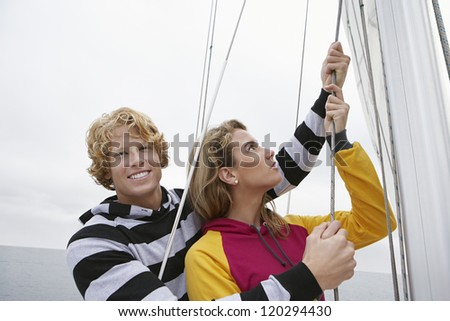 Happy Caucasian couple holding rope on sail boat - stock photo