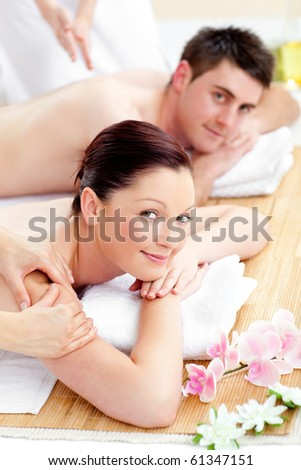 Happy caucasian couple receiving a back massage in a spa center - stock photo