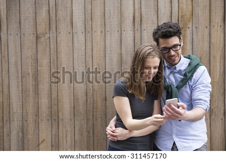 Happy Caucasian couple using a Smart Phone outdoors in the city. - stock photo