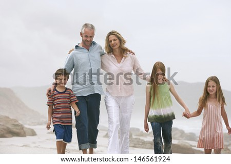Happy Caucasian couple walking with children at beach - stock photo