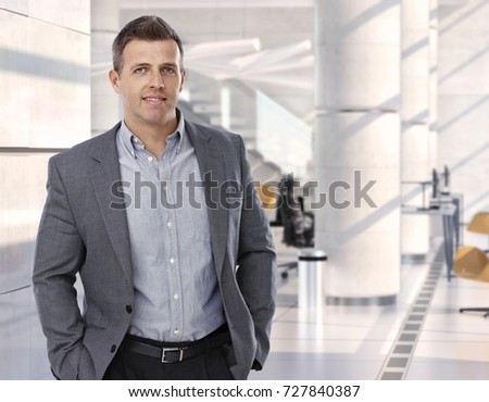 Happy caucasian customer waiting at bright business center lobby, standing, hands in pocket, smiling. Copyspace.