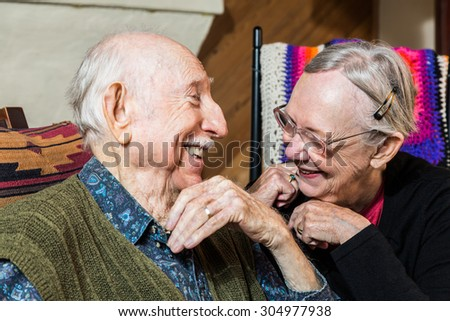 Happy Caucasian elderly couple sitting indoors smiling - stock photo