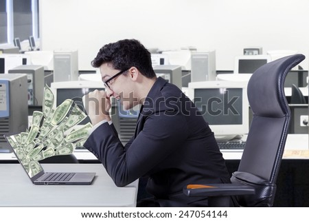 Happy caucasian entrepreneur looking money dollars on laptop computer at office - stock photo
