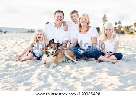 Happy Caucasian Family and Their Dog Portrait at the Beach. - stock photo